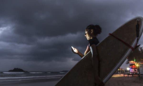Frau mit Surfboard unterm Arm nutzt Mobiltelefon für E-Learning