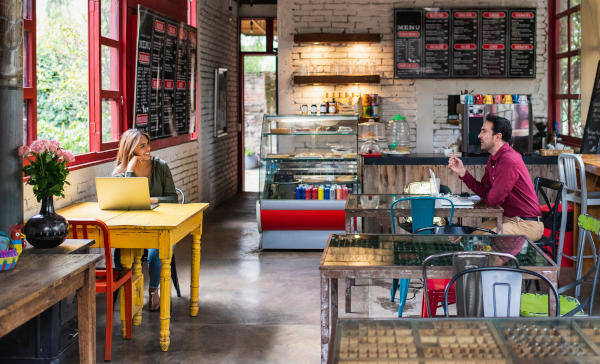 Mann und Frau unterhalten sich angeregt in einem Café sitzend