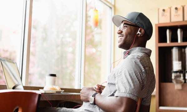 Mann sitzt lachend im Café und arbeitet am Laptop