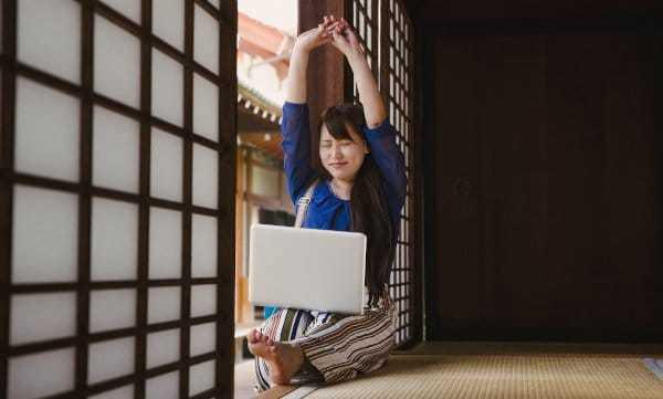 Sitzende junge Frau hat Laptop auf den Beinen und streckt sich mit geschlossenen Augen
